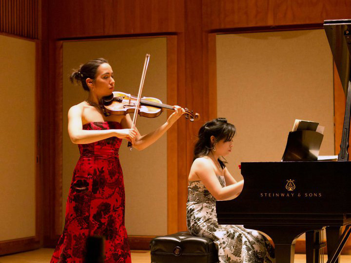 Sara Matayoshi playing the violin in a concert setting